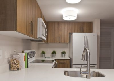Apartment kitchen with white quartz countertops and wood cabinets at Trinity Row